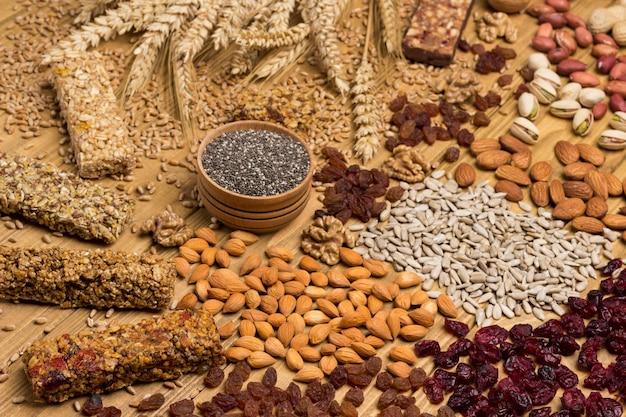 Snack vegano bilanciato, barretta proteica ai cereali. frutta a guscio, semi, cereali, quinoa nera, spighette di grano. concetto di perdita di peso. vista dall'alto. superficie in legno. avvicinamento