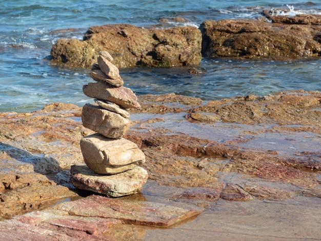 Pietre zen equilibrate sulla spiaggia con cielo azzurro e mare.