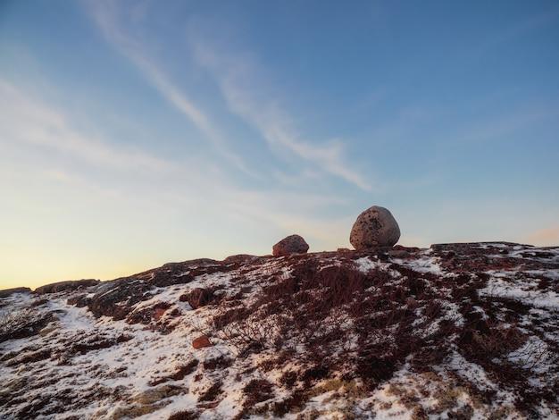 Balancing rock sulle colline artiche nel cielo polare. meraviglie incredibili nella natura.