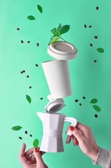 Bilanciamento della piramide del caffè zero rifiuti in mani femminili su aqua menthe. bollitore per caffè espresso in ceramica e tazza da caffè riutilizzabile ecologica da viaggio in bambù con coperchio.