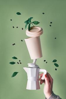 La piramide zero del caffè residuo di equilibratura ha tenuto dalla mano femminile sul fondo verde della menta. caffettiera in ceramica per caffè espresso e tazza da caffè in bambù riutilizzabile eco-compatibile. chicchi di caffè e foglie di piante.