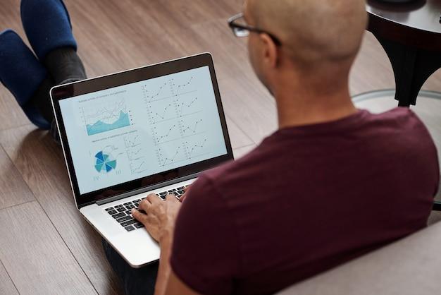 Imprenditore calvo nero seduto sul pavimento in camera da letto e lavorando al computer portatile e creando la relazione finanziaria annuale