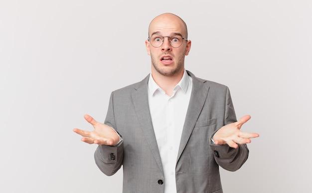 Uomo d'affari calvo che si sente estremamente scioccato e sorpreso, ansioso e in preda al panico, con uno sguardo stressato e inorridito