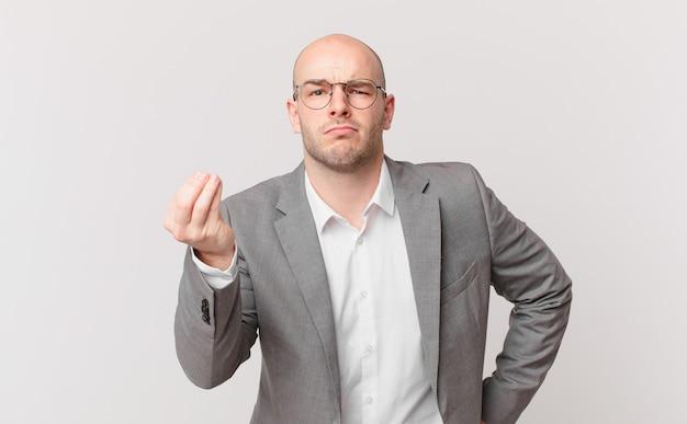 Uomo d'affari calvo che fa gesti o denaro, dicendoti di pagare i tuoi debiti!