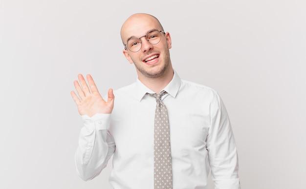 Uomo d'affari calvo che sorride allegramente e allegramente, agitando la mano, accogliendoti e salutandoti, o salutandoti