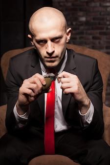 Assassino calvo in giacca e cravatta rossa pronto a tirare una spilla granata