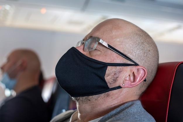 Uomo calvo in maschera medica nera e occhiali dorme sull'aereo turista addormentato sull'aereo