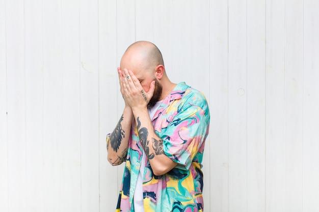 Uomo calvo che copre gli occhi con le mani con uno sguardo triste e frustrato di disperazione, pianto, vista laterale Foto Premium