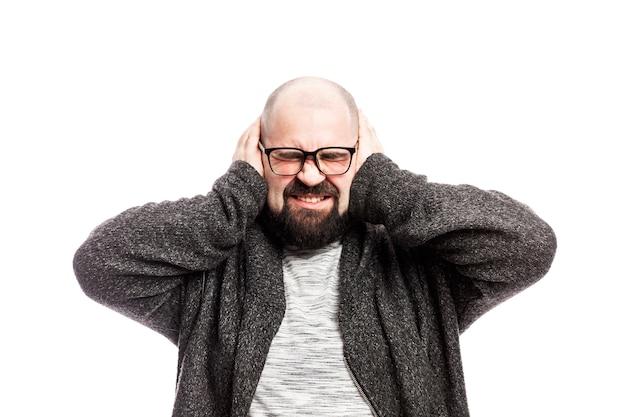 L'uomo calvo si coprì emotivamente le orecchie con le mani. isolato su un muro bianco
