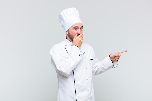 Uomo calvo che si sente felice, scioccato e sorpreso, coprendo la bocca con la mano e indicando lo spazio laterale della copia