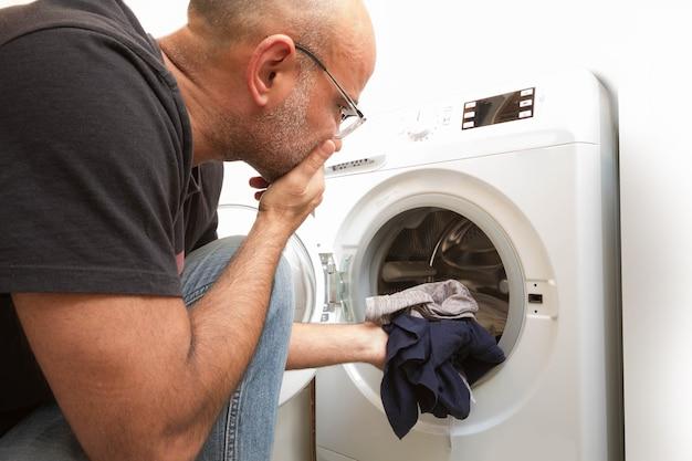 L'uomo calvo in jeans e maglietta grigi si siede davanti a una lavatrice a casa. caricare la lavatrice con panni sporchi. soggiorno luminoso e spazioso con interni moderni.
