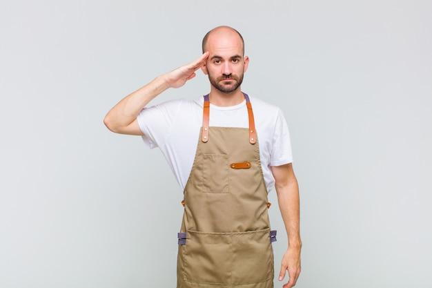 Uomo calvo che saluta la telecamera con un saluto militare in un atto di onore e patriottismo, mostrando rispetto