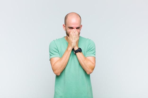 Uomo calvo che sembra felice, allegro, fortunato e sorpreso che copre la bocca con entrambe le mani