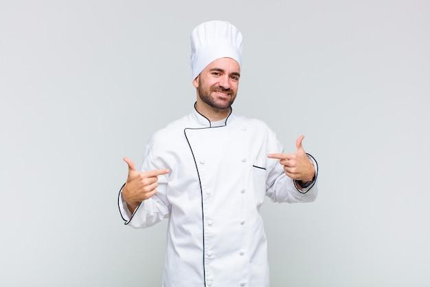 Uomo calvo che sembra orgoglioso, arrogante, felice, sorpreso e soddisfatto, indicando se stesso, sentendosi come un vincitore