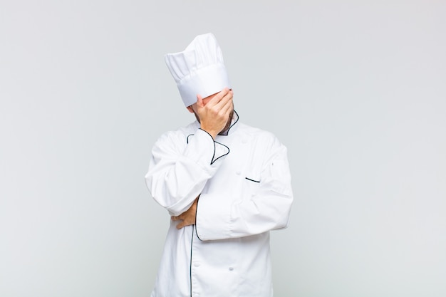 Uomo calvo che sembra stressato, vergognoso o turbato, con un mal di testa, che copre il viso con la mano