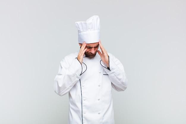 Uomo calvo che sembra stressato e frustrato, lavora sotto pressione con un mal di testa e tormentato dai problemi