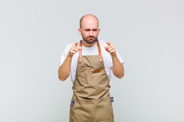 Uomo calvo che indica con entrambe le dita e l'espressione arrabbiata, dicendoti di fare il tuo dovere