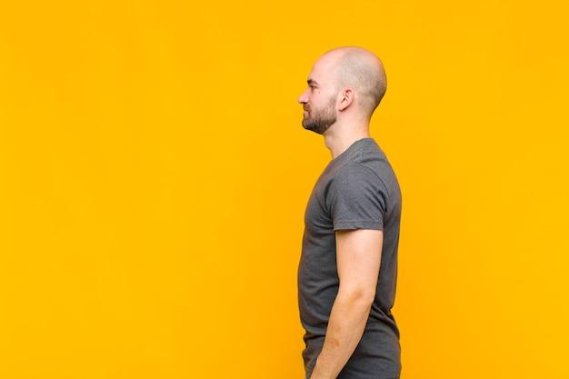Uomo calvo sulla vista di profilo che cerca di copiare lo spazio davanti, pensare, immaginare o sognare ad occhi aperti