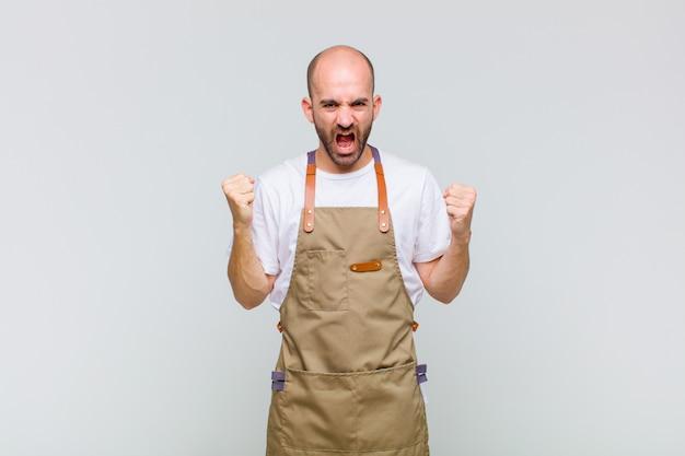 Uomo calvo che grida in modo aggressivo con un'espressione arrabbiata o con i pugni chiusi per celebrare il successo