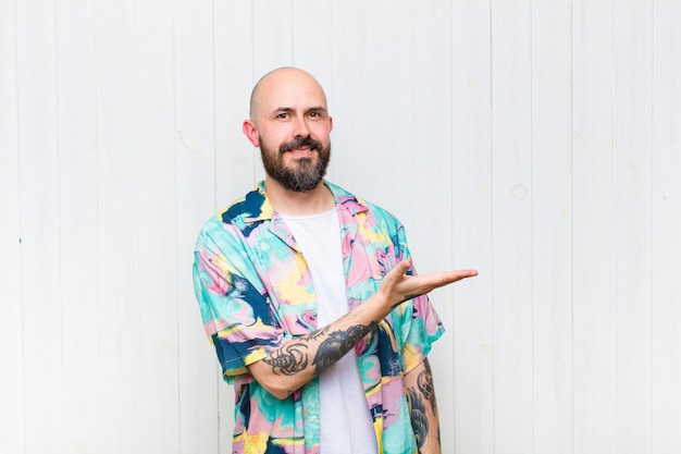 Uomo calvo che sorride allegramente, sentendosi felice e mostrando un concetto nello spazio della copia con il palmo della mano