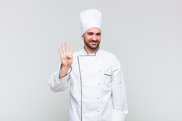 Uomo calvo che sorride e sembra amichevole, mostrando il numero quattro o quarto con la mano in avanti, conto alla rovescia