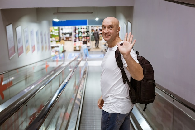 L'uomo calvo cammina lungo la scala mobile con uno zaino al centro commerciale