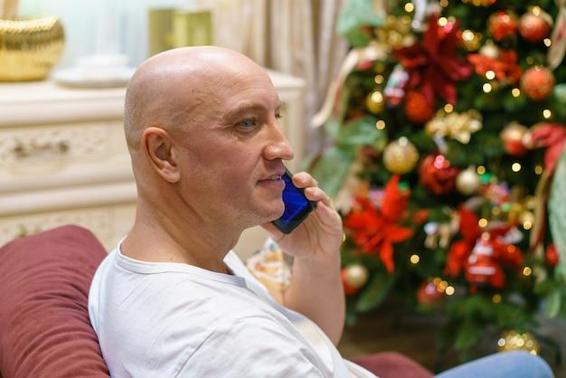 L'uomo calvo in maglietta bianca è seduto sul divano e parla al telefono sullo sfondo del natale tr...