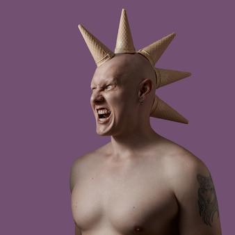 Un uomo calvo con un torso nudo con un cono gelato in testa su una parete viola. concetto di dente dolce o servizi di barbiere