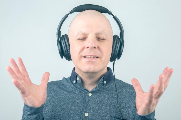 L'uomo calvo con gli occhi chiusi ascolta musica con le cuffie su uno sfondo chiaro