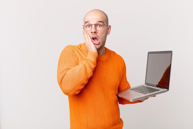 Uomo calvo con il computer che si sente scioccato e spaventato, sembra terrorizzato con la bocca aperta e le mani sulle guance