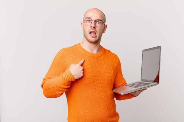 Uomo calvo con il computer che sembra scioccato e sorpreso con la bocca spalancata, che indica se stesso