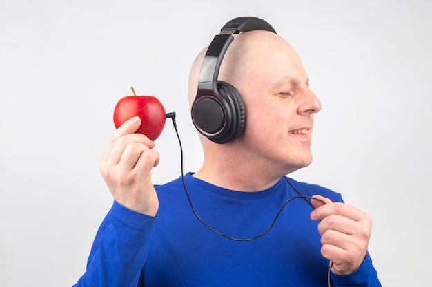 L'uomo calvo con le cuffie ascolta musica tramite un giocatore di mela rossa. metafora e concetto di benefici vitaminici nella musica e nel suono