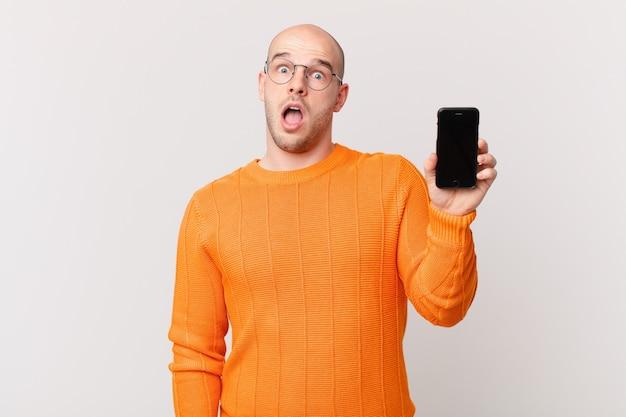 Uomo calvo con uno smartphone contro il muro isolato