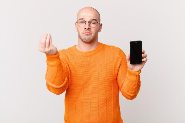 Uomo calvo con uno smartphone che fa un gesto di denaro o denaro, dicendoti di pagare i tuoi debiti!