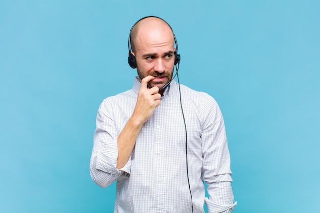 Uomo calvo con sguardo sorpreso, nervoso, preoccupato o spaventato, guardando di lato verso lo spazio della copia