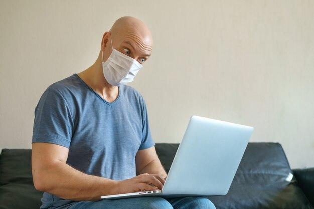 Un uomo calvo lavora a casa su un computer portatile su un divano in una maschera durante la quarantena. il concetto di lavoro a distanza