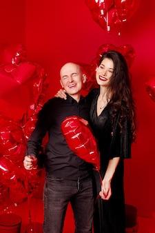 Uomo calvo e giovane donna in nero stanno con palloncini a forma di cuore