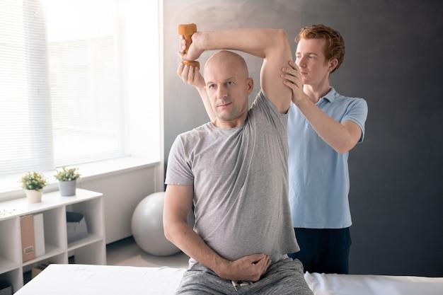 Uomo muscoloso calvo in abbigliamento sportivo seduto sul divano medico in cliniche di riabilitazione e facendo esercizio con manubri mentre il medico lo aiuta