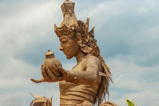 Bali, indonesia: statua di dewi sri, la dea del riso, realizzata con foglie di piante di riso essiccate, situata al centro delle terrazze di jatiluwih, patrimonio dell'unesco