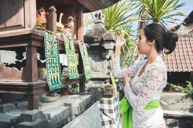 Donna balinese facendo rituale offrendo canari sari e pregando