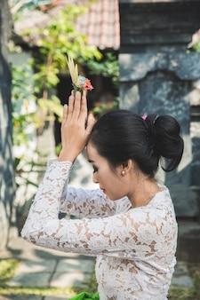 Tempio pregante della donna balinese su piccoli santuari nelle case