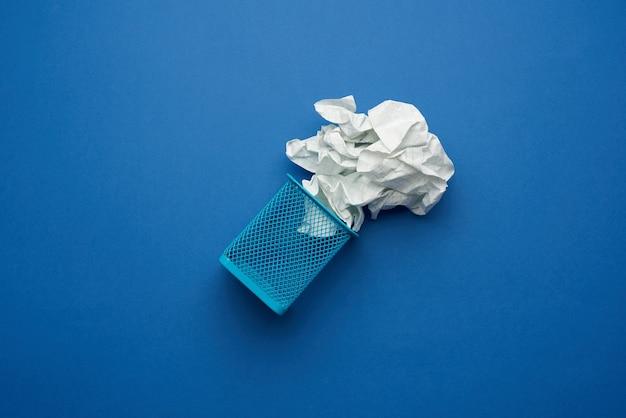 Sfera di carta bianca stropicciata e cestino dei rifiuti in metallo