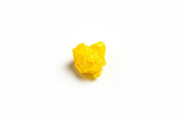 Palla di nastro adesivo giallo sgualcito su sfondo bianco. vista dall'alto, piatto.