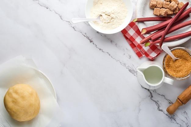 Palla di pasta e ingredienti farina, acqua, burro, zucchero e rabarbaro per la cottura su fondo di marmo bianco con spolverata di farina. ricetta passo dopo passo. messa a fuoco selettiva. vista dall'alto.
