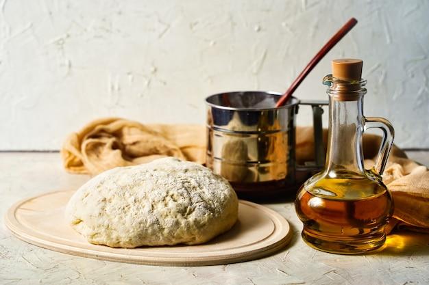 Palla di pasta sul tavolo della cucina olio d'oliva in una bottiglia che impasta la pasta della pizza pane rustico fatto in casa