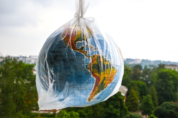 La palla a forma di globo è in un sacchetto di plastica come concetto di inquinamento plastico della terra