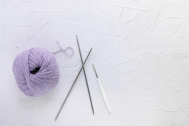 Gomitolo di lana lilla, uncinetto e aghi. lavoro a maglia, fatto a mano e hobby.