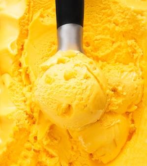 Una pallina di gelato al mango naturale in una scatola. sfondo di gelato arancione tropicale Foto Premium