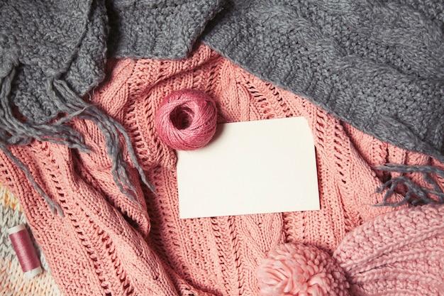 Gomitolo di lana rosa con carta bianca per il testo su sfondo rosa e grigio a maglia