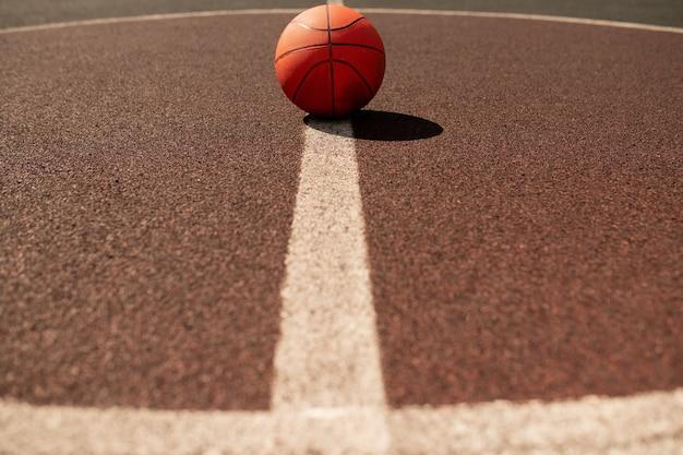 Palla per giocare a basket che si trova al centro della linea bianca verticale sul moderno stadio o campo